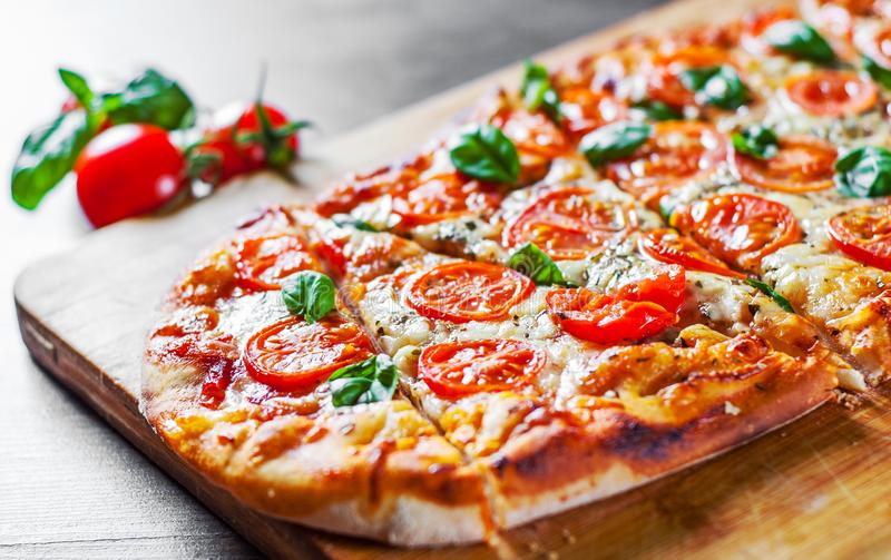 Oval Pizza with Mozzarella cheese, Tomatoes, pepper, Spices and Fresh Basil. Italian pizza. Pizza Margherita or Margarita on woode royalty free stock image