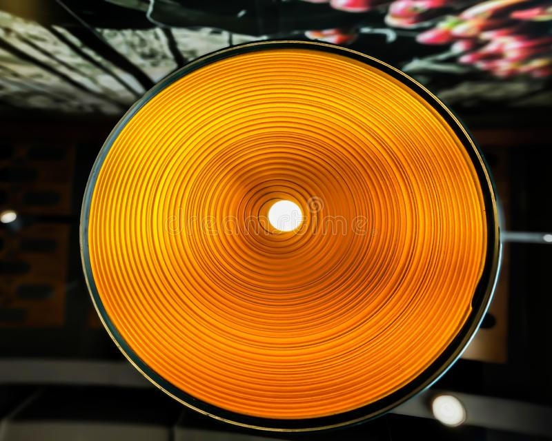 Oval shape hanging light in a coffee shop. Beautiful oval shape hanging light in a coffee shop with orange stripes stock photos