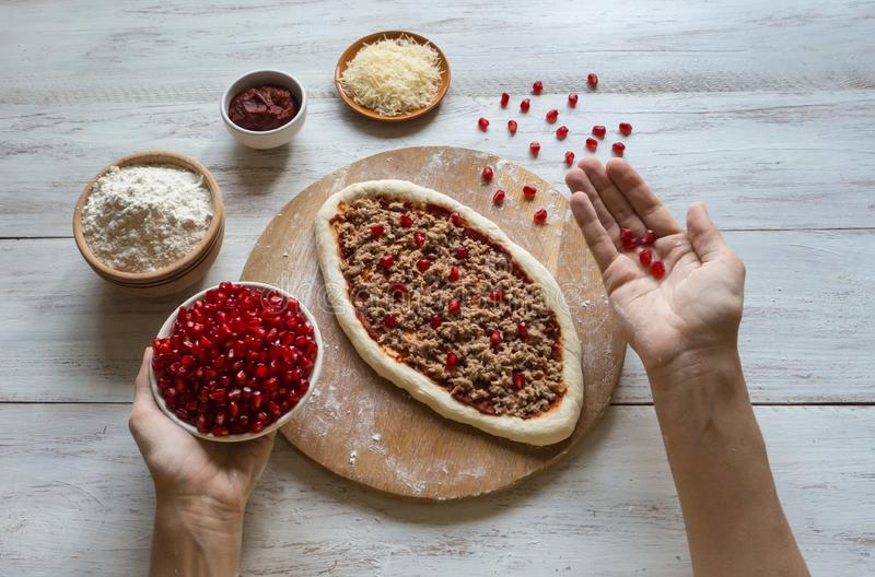 Oval shape tuna pizza decorated with pomegranate seeds. Cooking pizza. royalty free stock photography