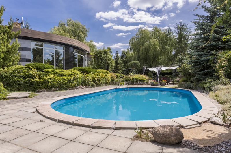 Oval swimming pool in big garden stock photo image of house trees 89606146 for Large swimming pools for gardens