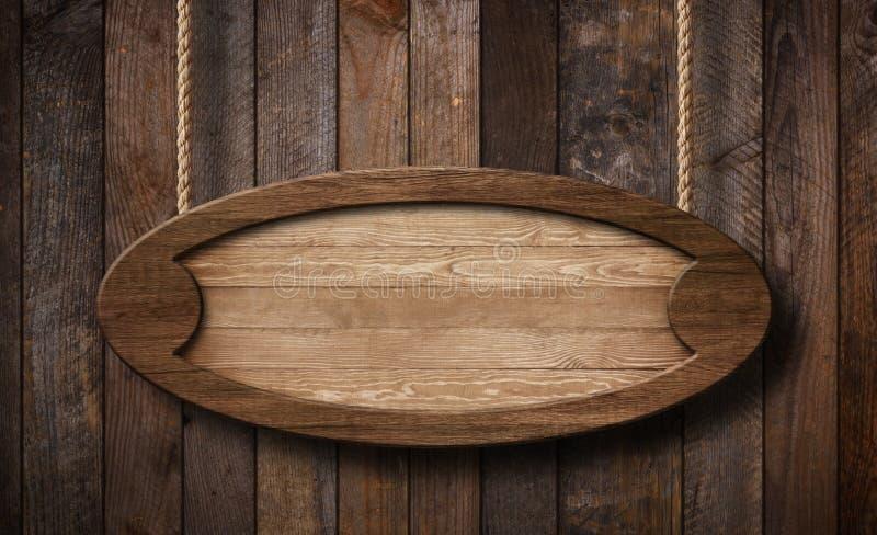 Ovales Holzschild, das an den Seilen mit hölzernem Plankenhintergrund hängt stockbild