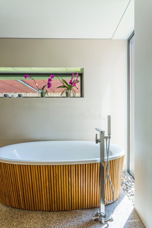 Ovalt badkar med träbilaga royaltyfri bild
