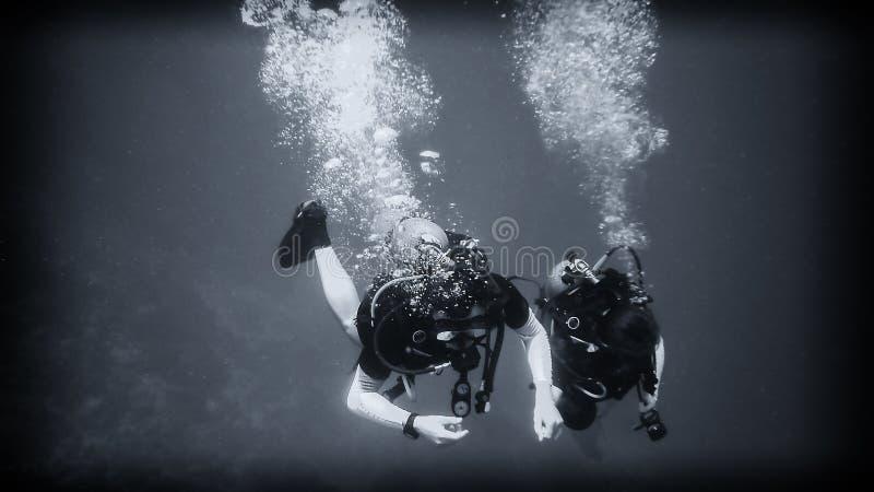 Ovanför avgrunden en dykare under vatten arkivfoto