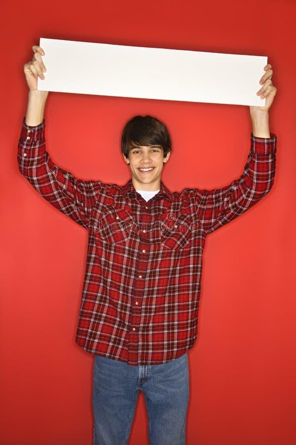 ovanför det caucasian huvudet för blank pojke hans teen holdingtecken royaltyfri foto