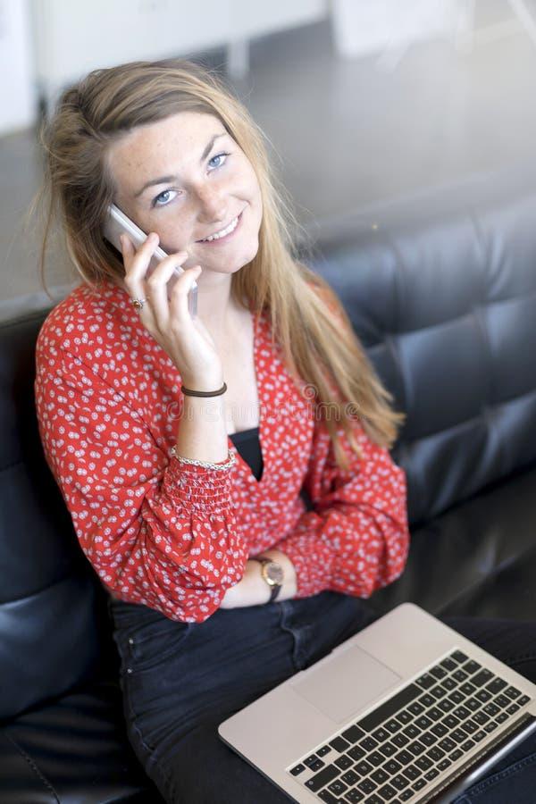 Ovanför sikt av en kvinna som använder en smartphone, medan tala och sitta på en soffa i vardagsrummet hemma royaltyfria bilder