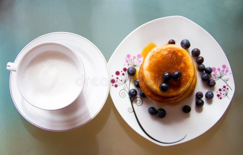 Ovanför sikt av plattan med koppen av krämigt kaffe och plattan med söta pannkakor som täckas av blåbärfrukter och lönnsirap arkivbilder