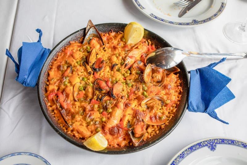Ovanför sikt av typisk spansk paella med den havs- musslan, räkan, humret, tioarmade bläckfisken, musslan, ris och citronen som ä royaltyfri bild