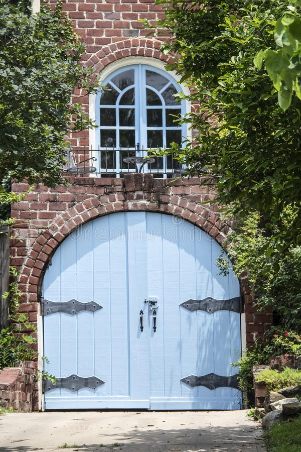 Ovanlig blå trävälvd garagedörr med stora utsmyckade gångjärn i tegelstenhus med den lilla balkongen med tabellen och stolar dire royaltyfria bilder