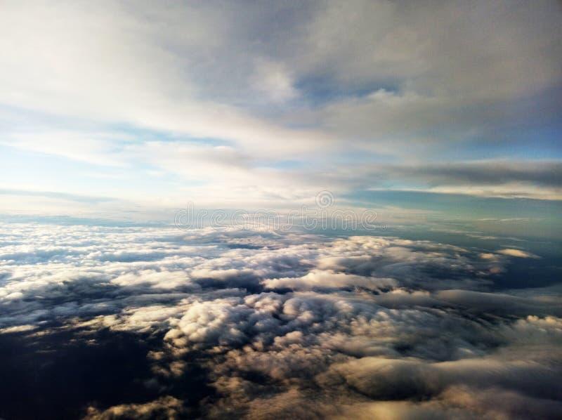 Ovanlig flyg- sikt av moln och blåa himlar ovanför jorden arkivfoton