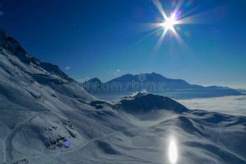 Ovanlig glorialjuseffekt, solen reflekterar av snön och skapar en ljus pelare av den ljusa höjdpunkten i bergen arkivbilder