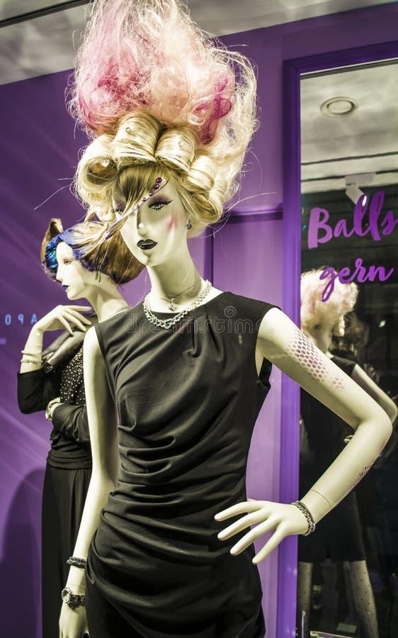 Ovanliga attrapper och original- frisyr Flickan med rosa hår och i en svart klänning modernt mode arkivfoto