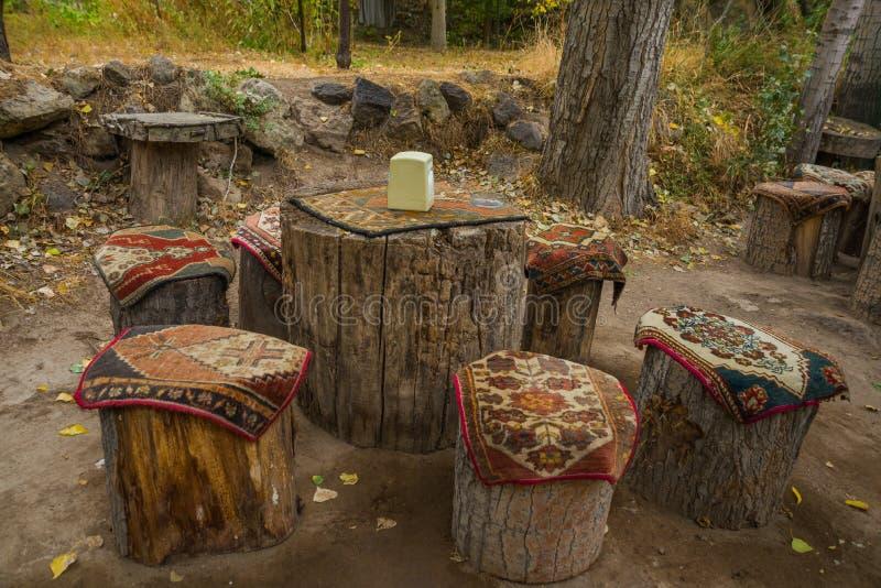 Ovanliga tabeller och stolar som göras av hampa, överst av traditionella uddemattor med en modell Cappadocia Turkiet fotografering för bildbyråer