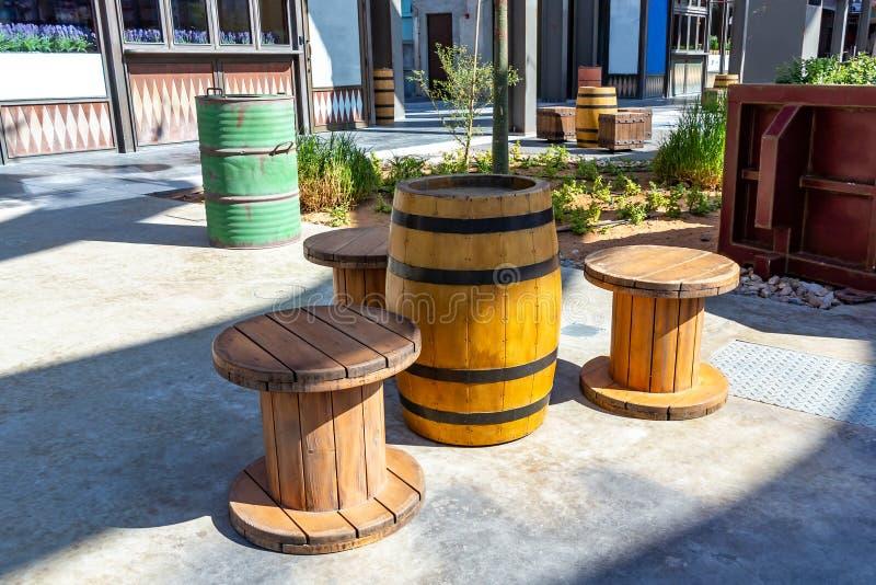 Ovanligt offentligt utrymme i staden - en tabell av gamla trummor och stolar av stora spolar för rep royaltyfria foton