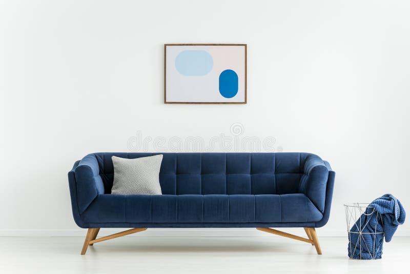 Ovannämnd blå soffa för affisch med kudden i den vita vardagsruminre med filten i korg Verkligt foto arkivbilder