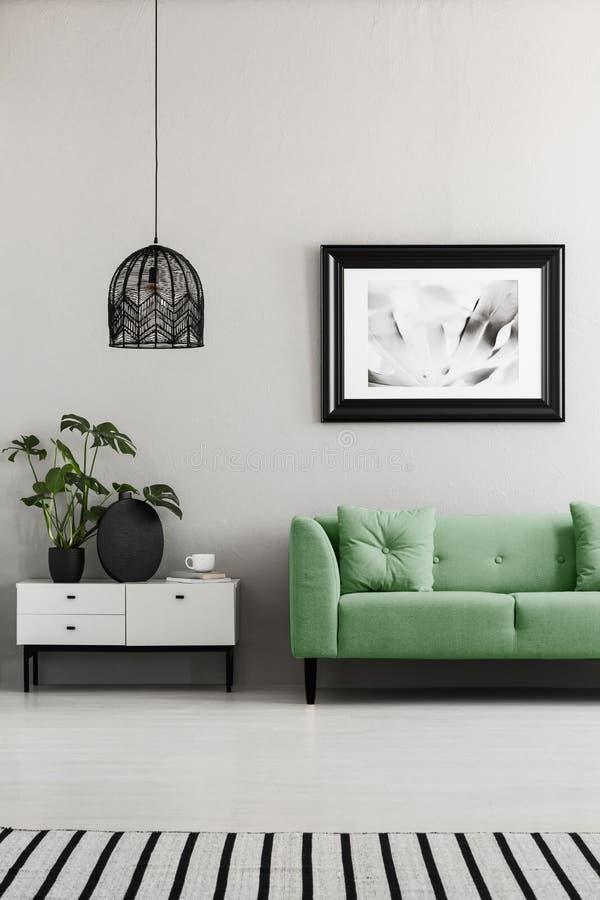 Ovannämnd grön soffa för affisch bredvid skåp med växter i vardagsruminre med lampan Verkligt foto royaltyfria foton