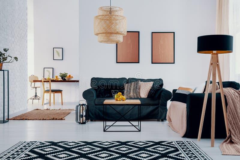 Ovannämnd grön soffa för rosa affischer i ljus lägenhetinre med mönstrad matta och lampan Verkligt foto royaltyfri bild