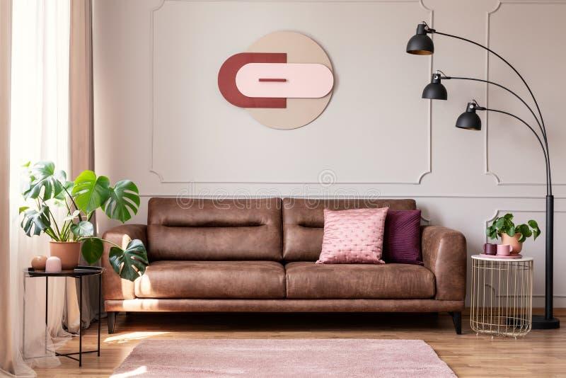 Ovannämnd lädersoffa för affisch med kuddar i vitlägenhetinre med växter och lampan fotografering för bildbyråer