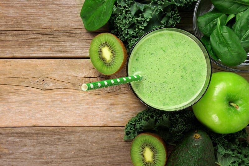 Ovannämnd sikt för grön smoothie med ingredienser över lantligt trä royaltyfri bild