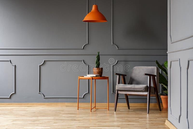 Ovannämnd tabell för orange lampa med växten bredvid fåtöljen i grå färger apar fotografering för bildbyråer