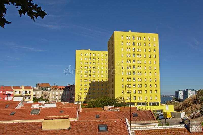 Ovannämnda tak för gul lägenhetblockstower av det normalahus i förortsofen Lissabon royaltyfri bild