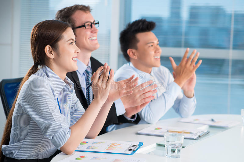 Ovation. Image of business partners applauding at the meeting sitting in a line royalty free stock photography