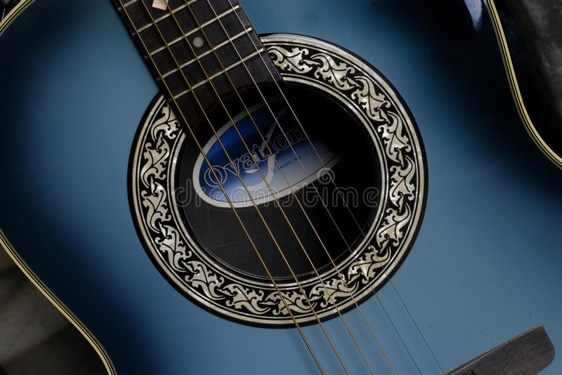 Close up of Ovation guitar. Ovation six string blue guitar close up with strings and nmae of instrumant inside guitar royalty free stock photo