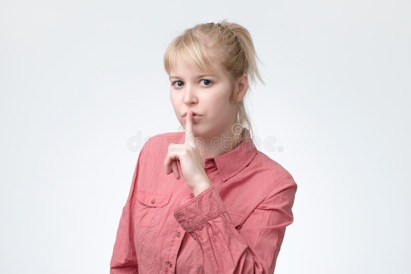 Ovely frågar den blonda kvinnlign att hålla hemlig information den förtroliga iklädda rosa skjortan arkivfoton