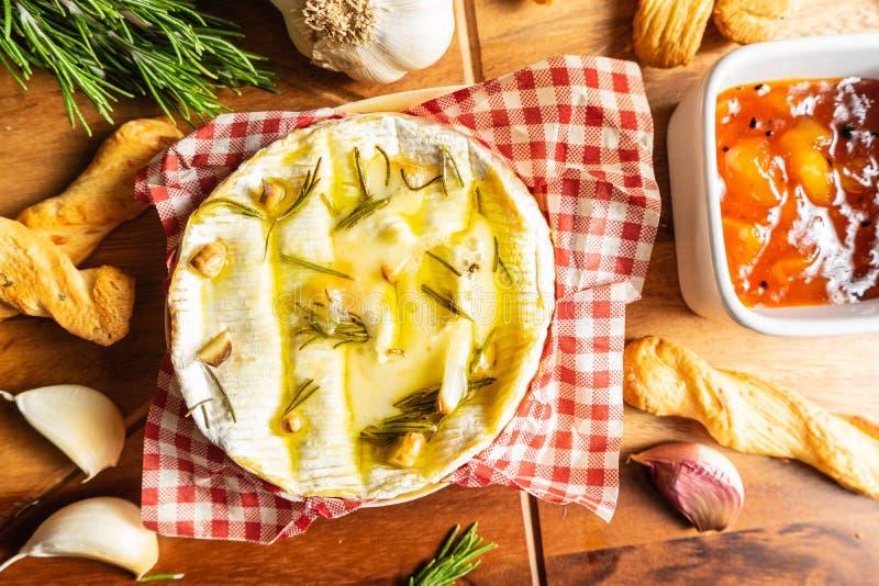 Oven Baked Camembert med vitlök, rosmarin och chutney royaltyfri bild