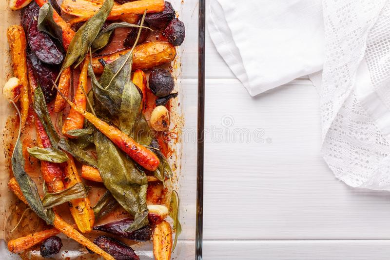 Oven baked carrots and beetroots with sage leaves and garlic royalty free stock photo