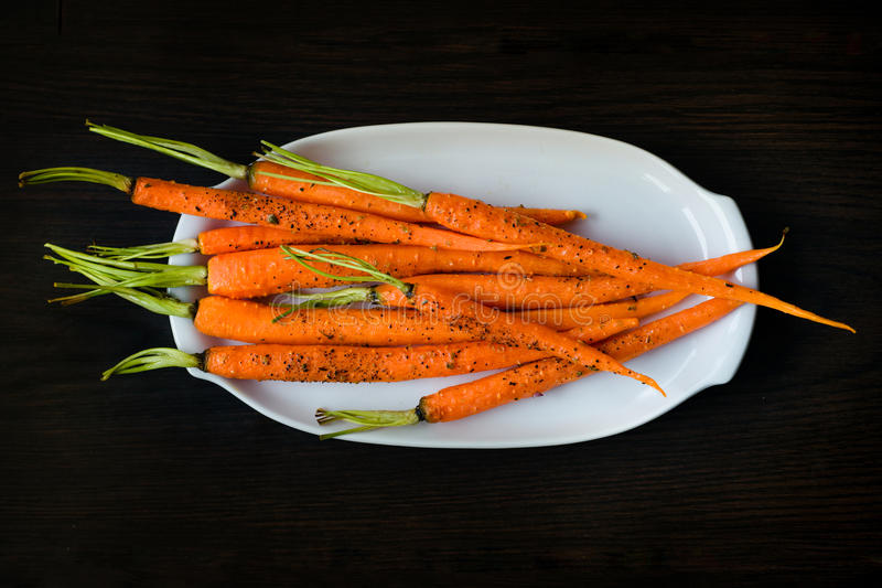 Oven-baked carrots sprinkled with fresh-grounded black pepper stock photography