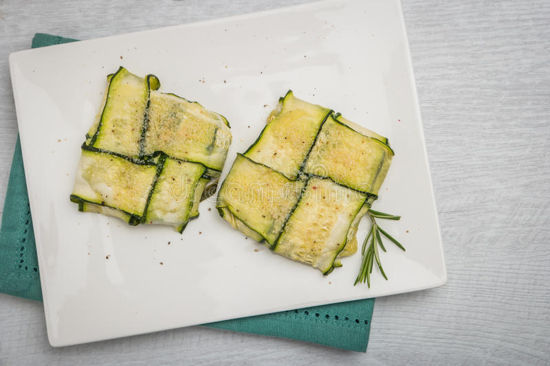 Oven baked courgetes. Oven baked courgettes stuffed with cheese, garlic and herbs. Courgette recipe in the oven. Top view with copy space royalty free stock photography