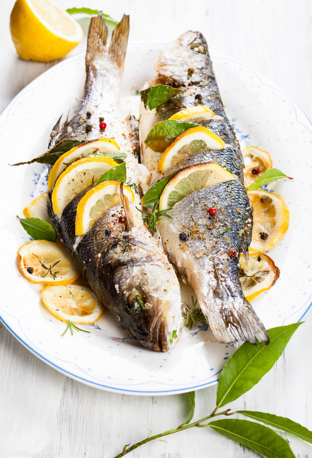 Oven-baked Sea bass. With lemon and herbs stock images