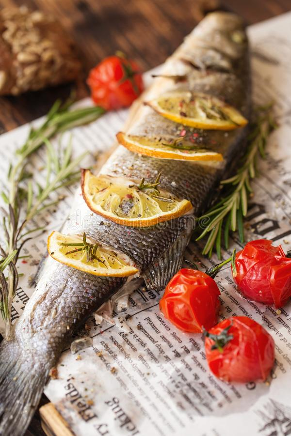Oven-baked Sea bass with lemon and herbs. fish, baked entirely stock photo