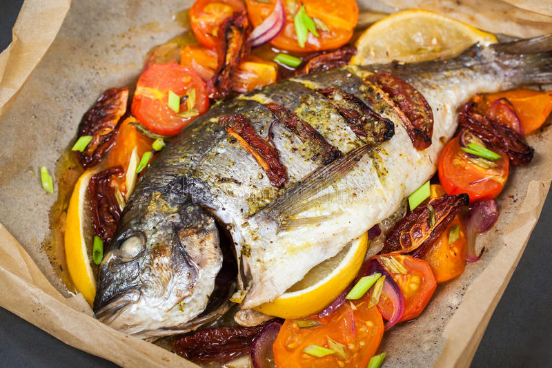 Oven baked whole sea bream fish with vegetables stock photography