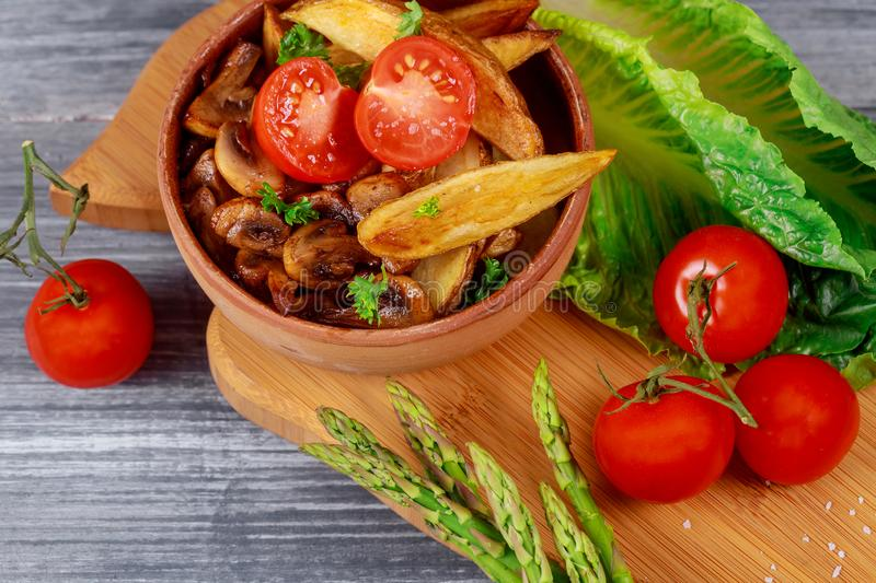 Oven fried potatoes and roasted mushrooms, fresh vegetables grilling stock image