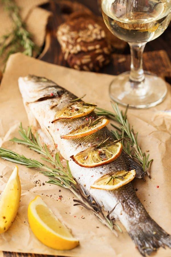 Oven-gebakken Overzeese baarzen met citroen en kruiden volledig gebakken vissen, stock foto's