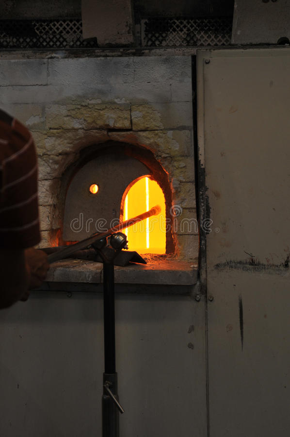 Oven in a glass making factory. Worker on an oven in a glass making factory royalty free stock photos