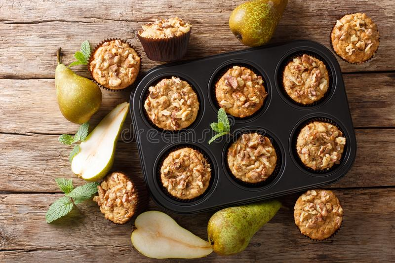 Only from the oven pear muffins with walnuts, cinnamon and nutmeg in a baking dish close-up. Horizontal top view stock photo