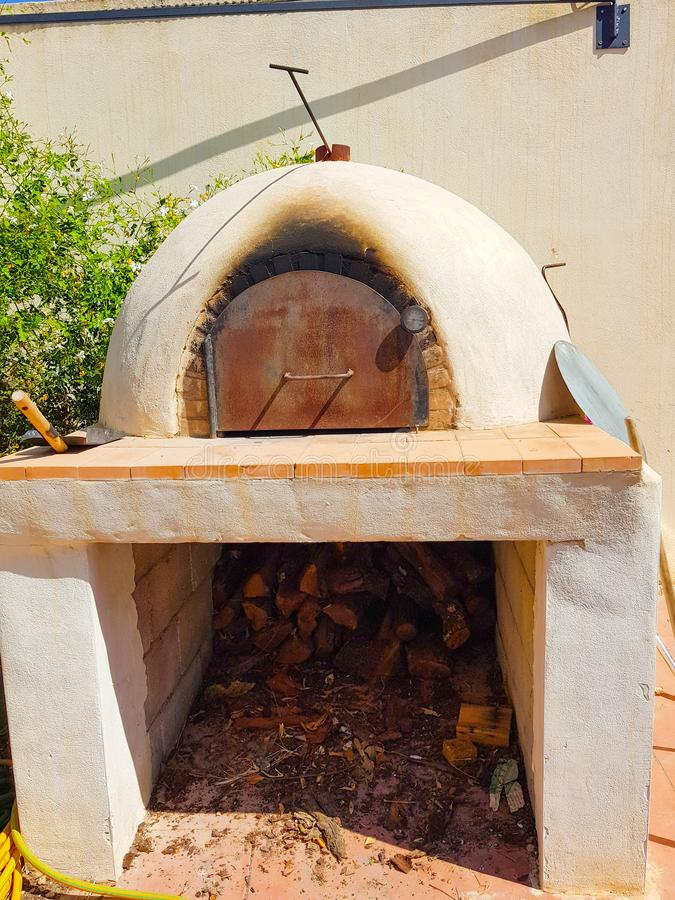 Oven for pizza and bread on the outside of a house. Situated next to a white wall. Hot, kitchen, wood, stove, cooking, food, old, fuel, bake, style, indoor stock images