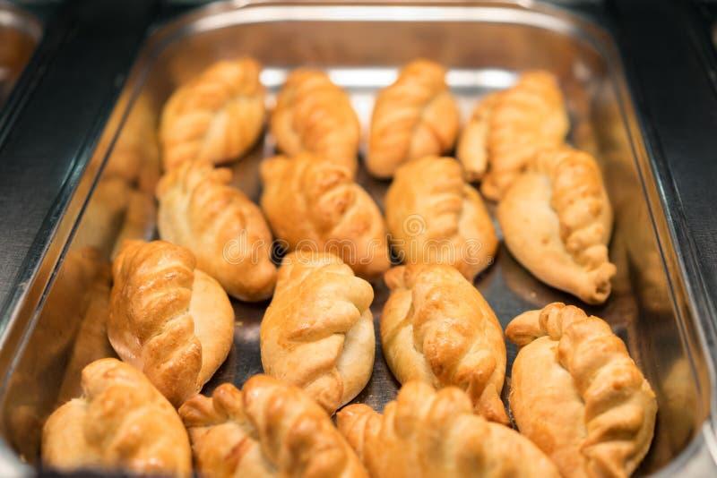 Oven verse gebakken pasteitjes Heerlijke gebakjes op een bakselblad Russische pirozhki of gebakken pasteitjes Traditionele Rus stock afbeelding