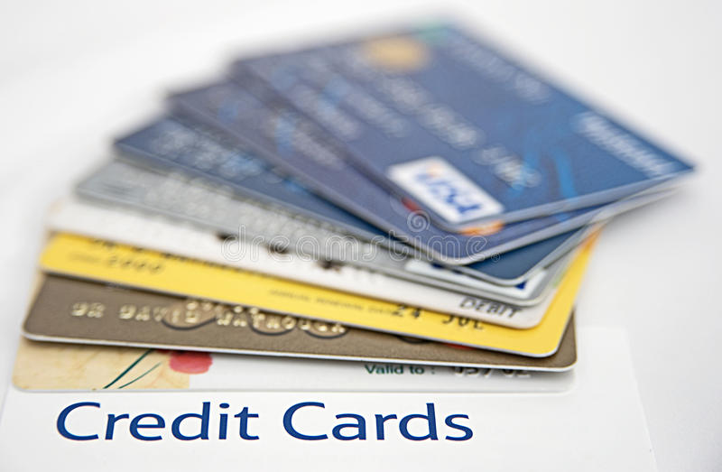 Over borrowed on credit cards. A macro image with selective focus on the text ' Credit Cards ' in bold blue letters with seven cards fanned out above it royalty free stock image