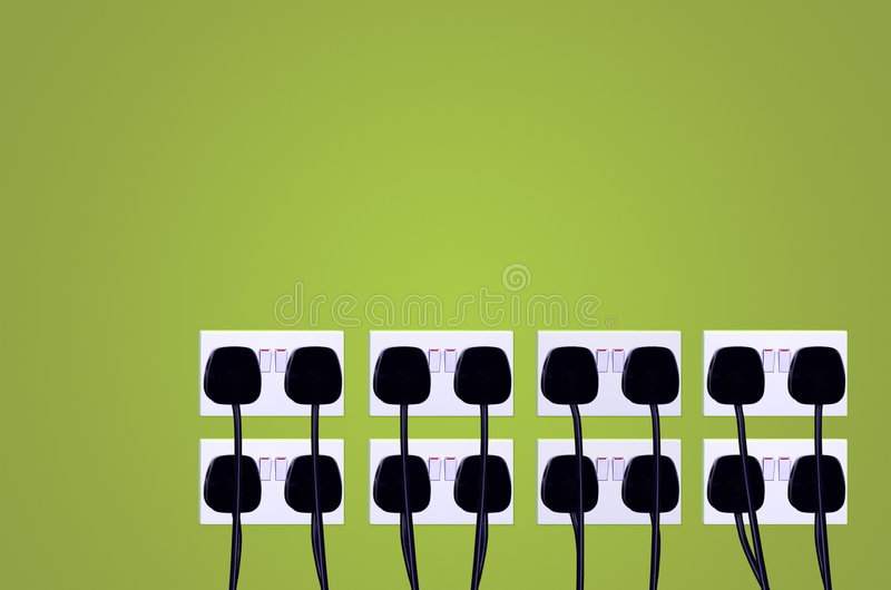 Over Consumption. Electrical sockets and plugs against a green wall. Energy consumption concept stock photo