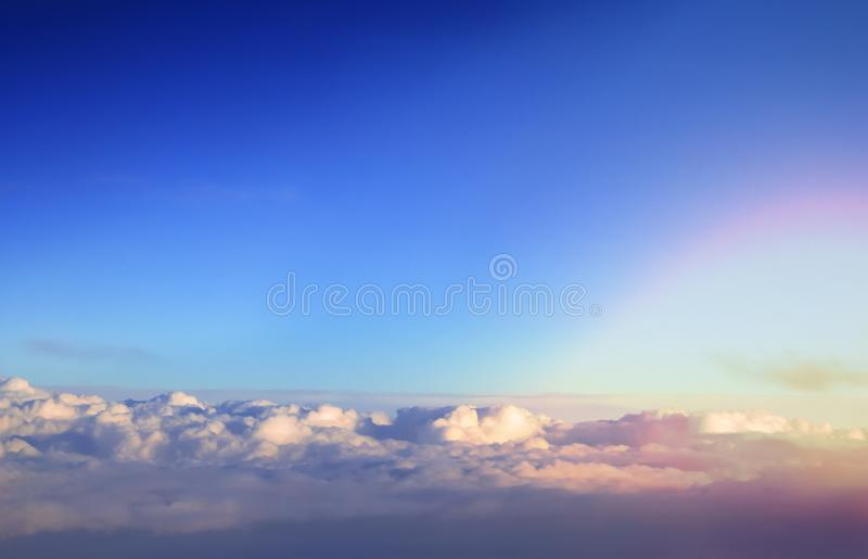Over cumulus clouds bright landscape view from the window of an airplane. royalty free stock photography