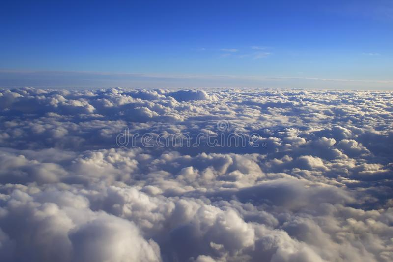 Over cumulus clouds bright landscape view from the window of an airplane. stock images
