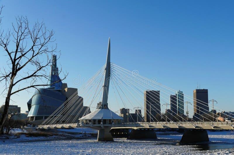 Over de Rode Rivier De wintermening over Promenaderiel brug met Canadees Museum voor Rechten van de mens op de achtergrond royalty-vrije stock afbeeldingen