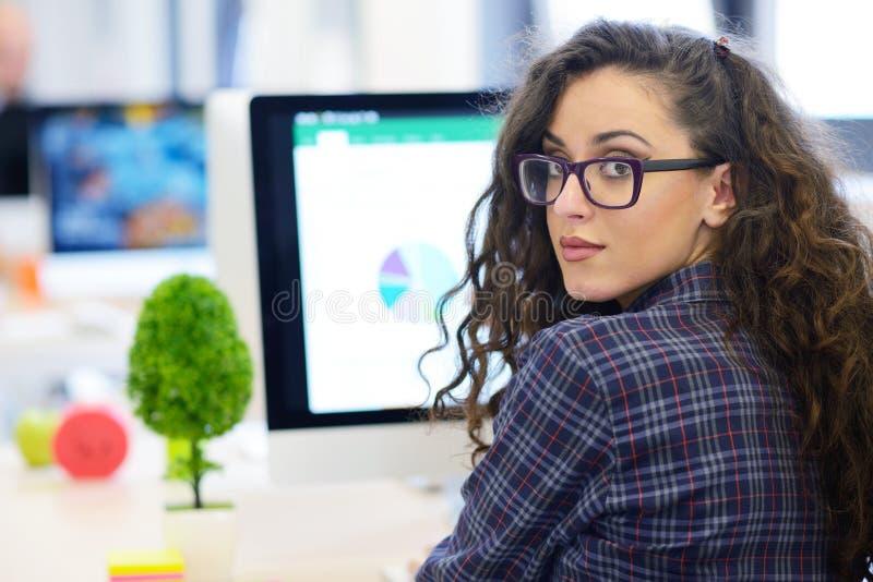 Over de schoudermening van een onderneemster die bij computer werken en aan grafiek richten royalty-vrije stock foto