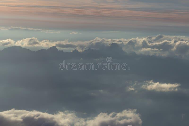 Over de wolken Fantastische achtergrond met wolken en bergpieken stock afbeelding