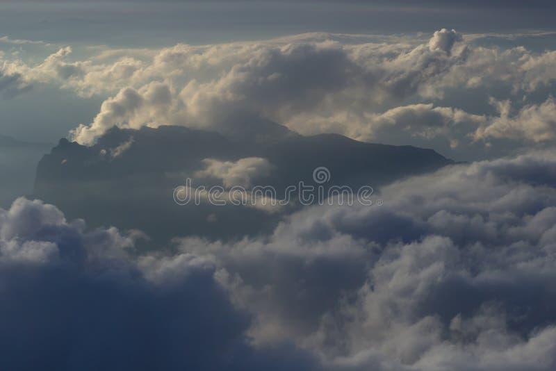 Over de wolken Fantastische achtergrond met wolken en bergpieken stock foto's