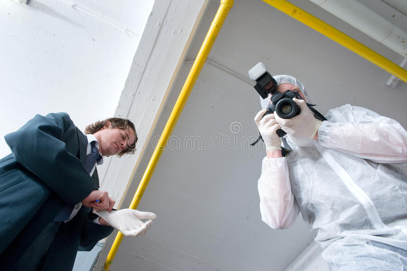 Over a dead body. Two policemen hovering over a dead body. A police lieutenant putting on his rubber gloves, and a forensics experts taking pictures of the royalty free stock photo