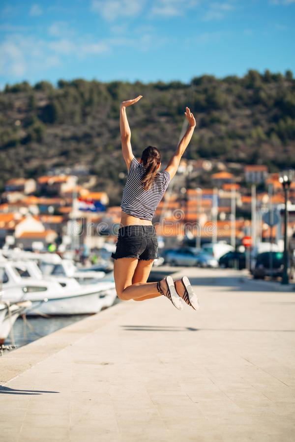 Over exited happy woman jumping in the air out of happiness. Vacation time concept. Seaside coastal vacation excitement. Woman in royalty free stock images